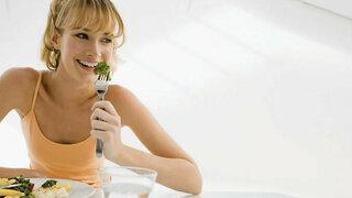 Junge Frau isst Brokkoli