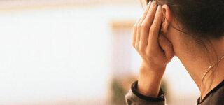 Frau stützt Kopf in die Hand