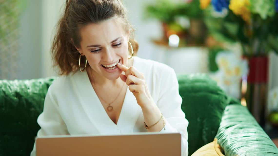 Frau am Laptop spricht mit ihrem Zahnarzt