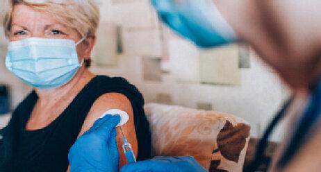 Corona Impfung im Pflegeheim Seniorenheim Impfdosis Seniorin Mundschutz Hanschuhe Pflegeeinrichtung