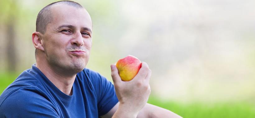 Mann isst Apfel