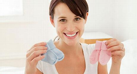 Schwangere hält rosa und hellbaue Söckchen hoch