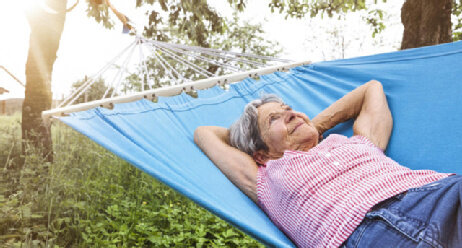 Seniorin liegt in einer Hängematte