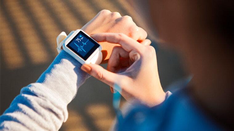 Frau überprüft die Herzfrequenz an einer Smartwatch