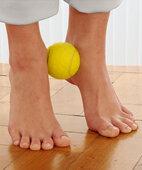 Fußgymnastik-Tennisball zwischen den Knöcheln halten