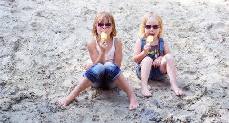 Geschwister sitzen am Strand und essen Eis