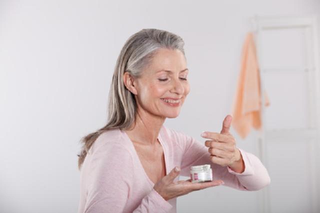 Frau um die Fünfzig cremt ihr Gesicht ein: Im Alter wird die Haut oft trockener und benötigt mehr Pflege