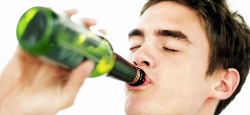 Junger Mann trinkt Alkohol