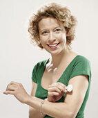 Frau klebt sich Nikotinpflaster auf den Oberarm
